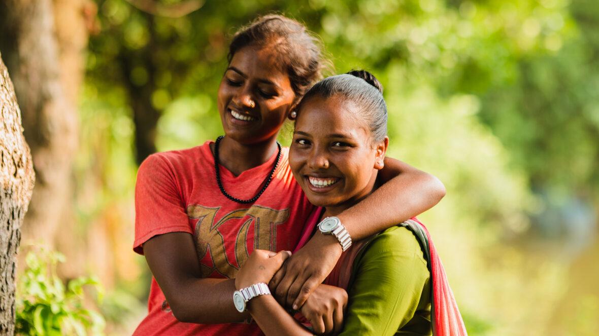 Kaksi nepalilaista tyttöä halaa hymyillen.
