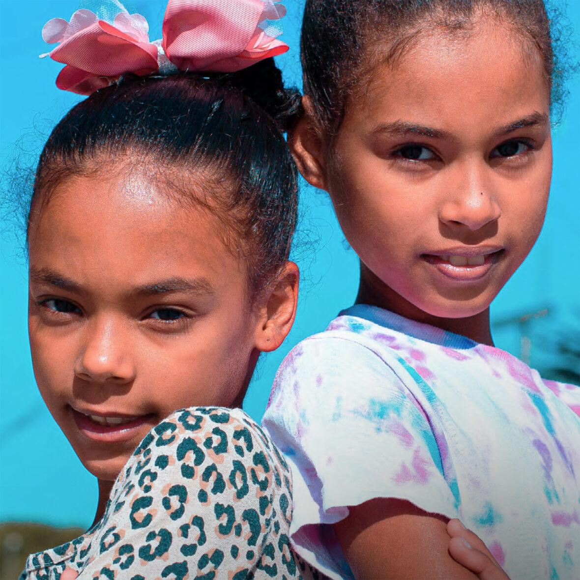 Kaksi tyttöä katsoo kameraan. Toisella on rusetti päässä.