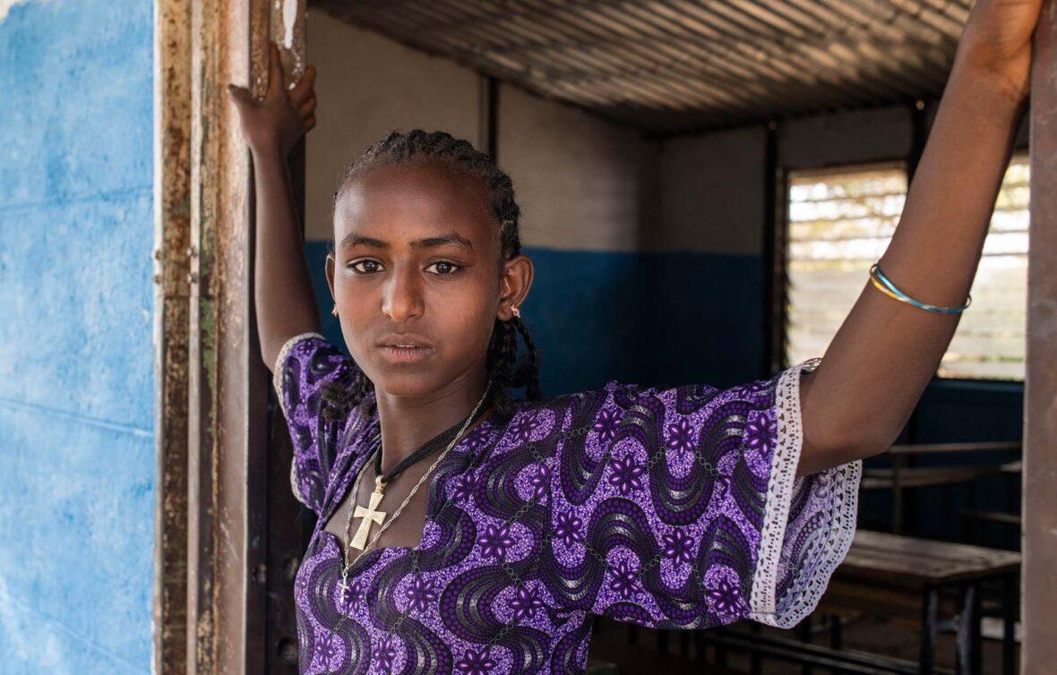 Etiopialainen tyttö seisoo rakennuksen oviaukossa ja katsoo vakavana kameraan.