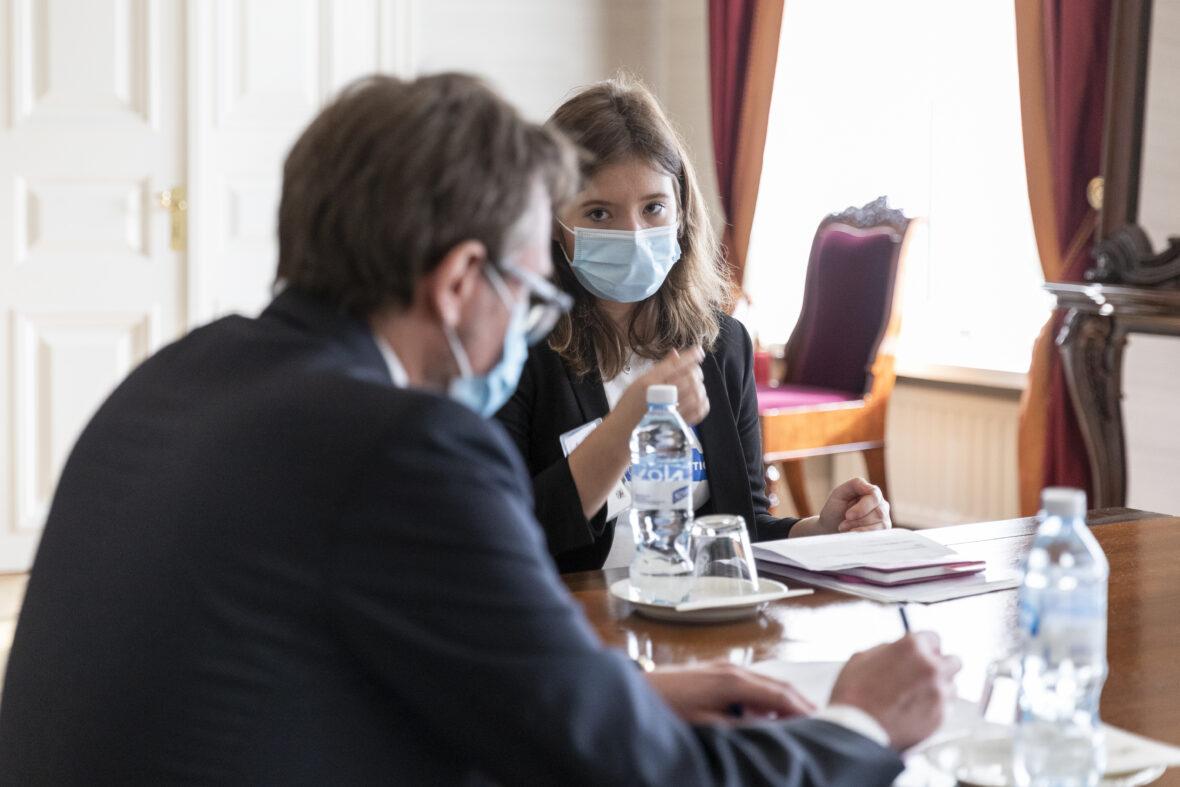Nella Salminen kabinettipöydän päässä, etualalla näkyy toinen henkilö.