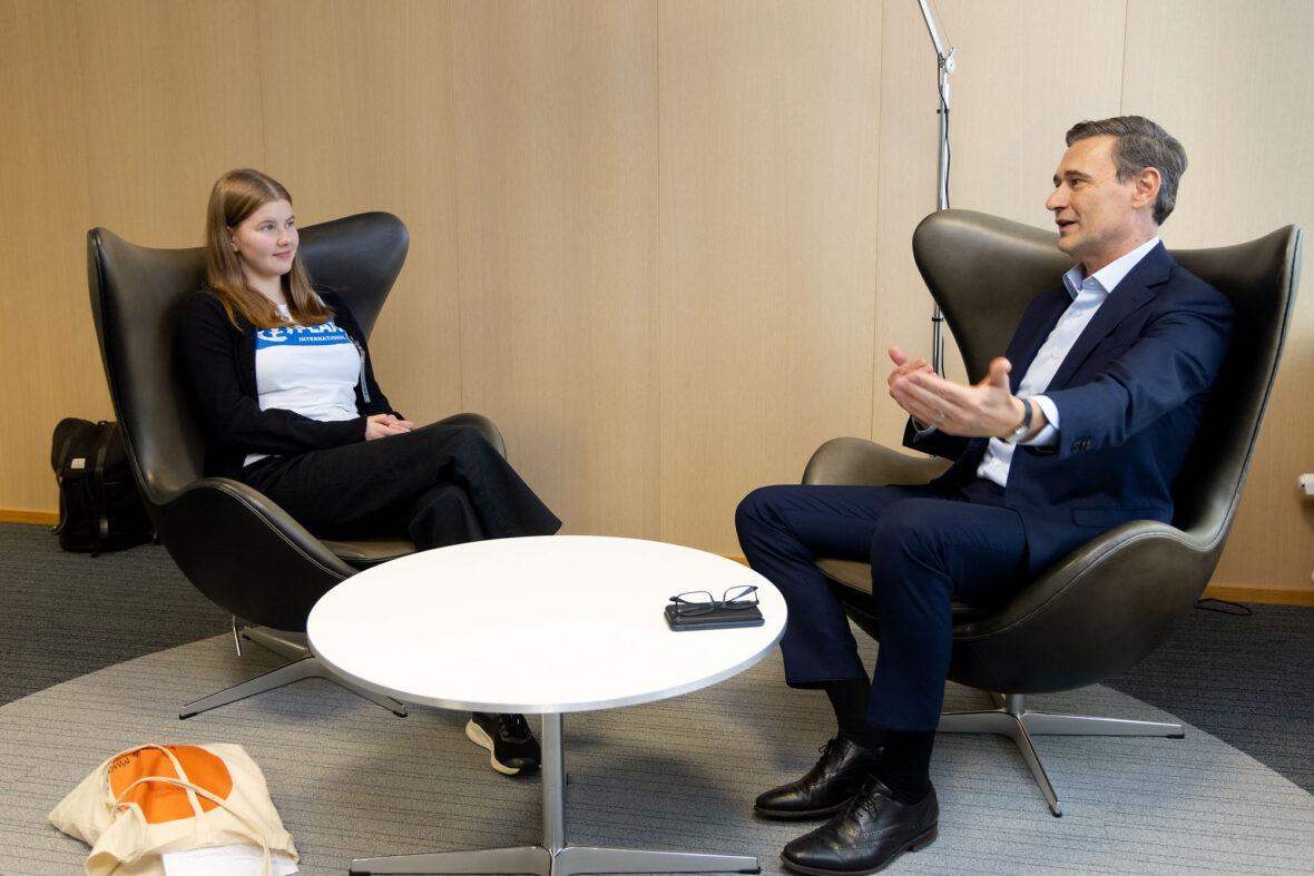 Planin nuori Martta Lyytinen ja Nesteen toimitusjohtaja Peter Vanacker keskustelevat pöydän ääressä.