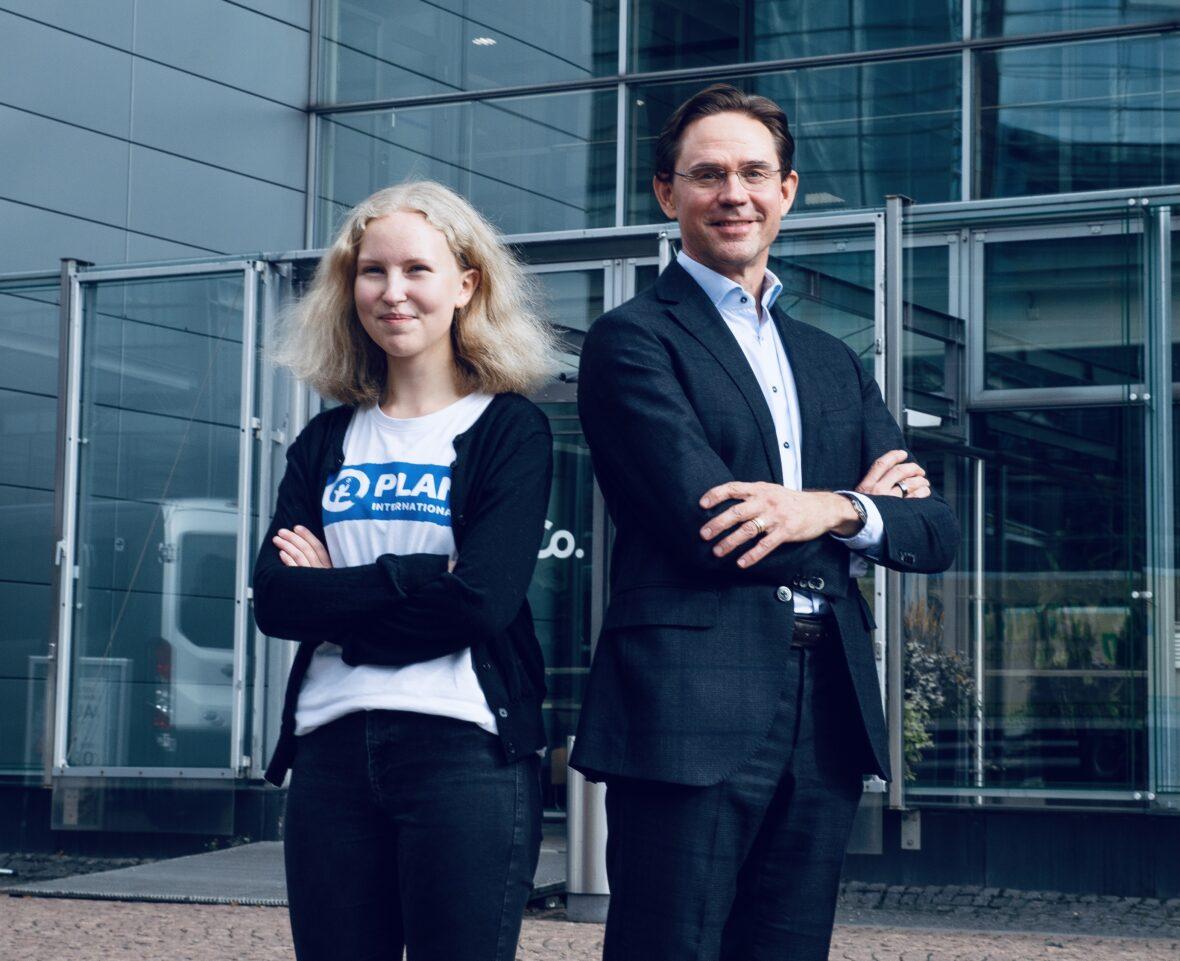 Planin nuori Martta Pyykönen ja Sitra yliasiamies Jyrki Katainen seisovat selät vastakkain Sitran pääoven edessä.